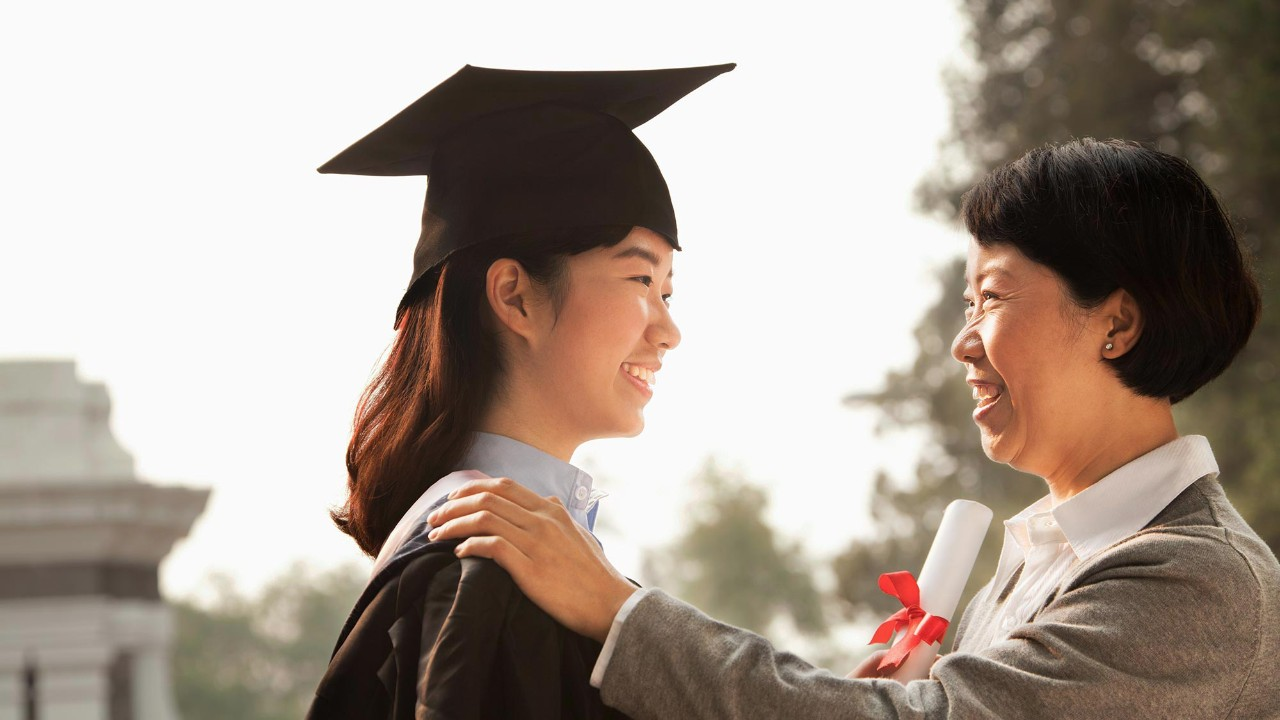 mother with hands on smiling grad's shoulders; image used for HSBC International Services Study abroad graduates'